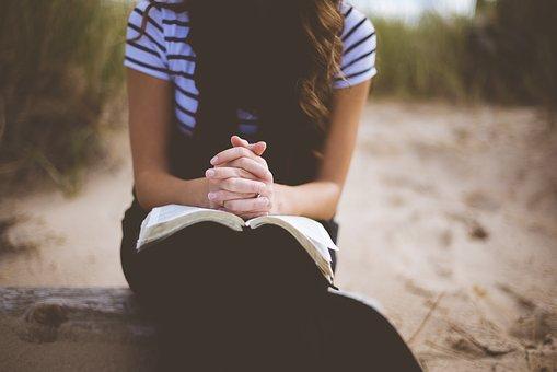 Imagem mostra mulher sentada de cabeça baixa orando com a Bíblia aberta.